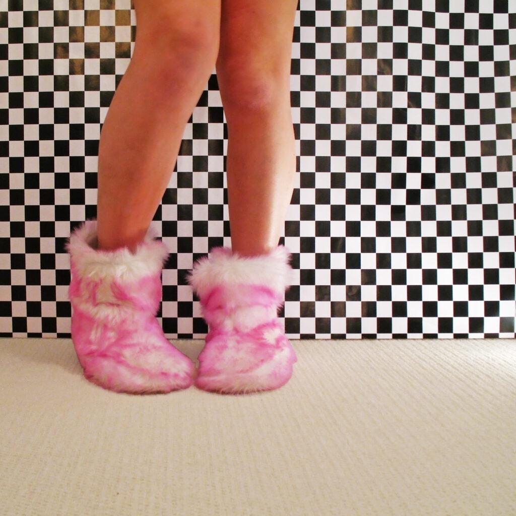 glatte Beine in kuscheligen Hausschuhen