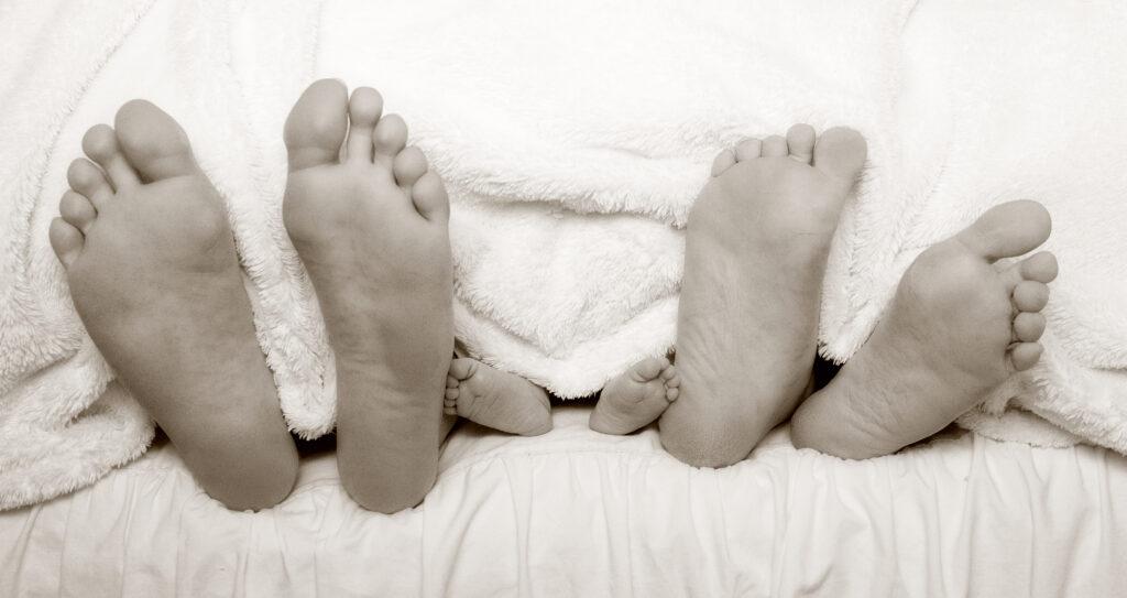 Papa, Kind und Mamas Füsse gucken aus dem Bett raus