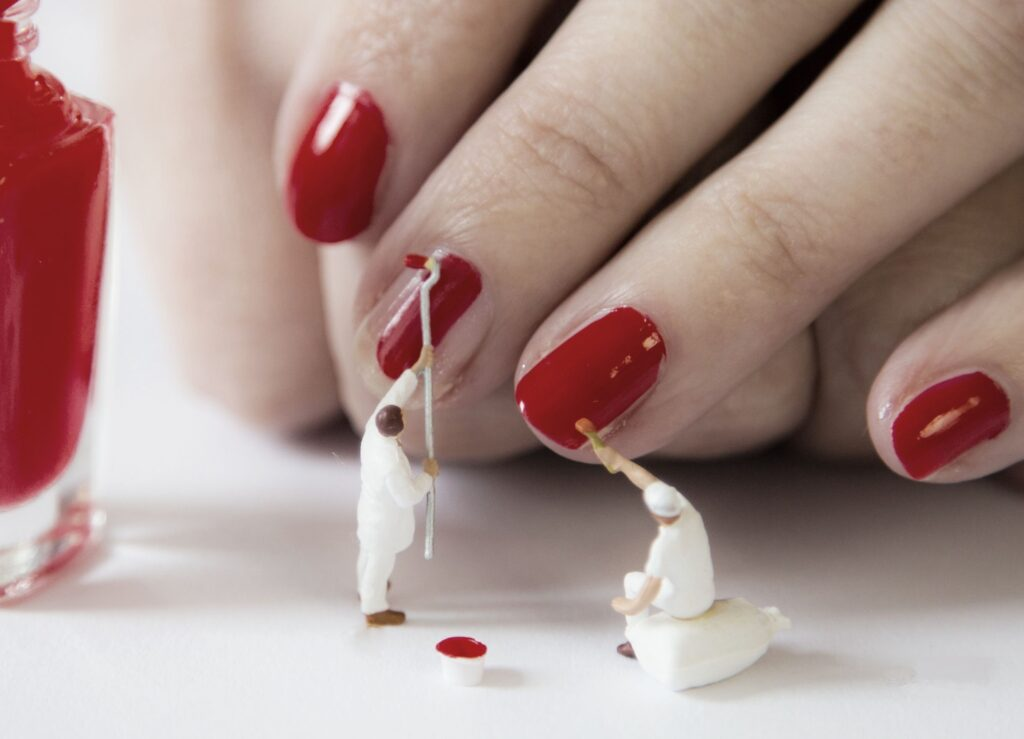 Arbeiter die mit roten Nägeln beschäftigt sind